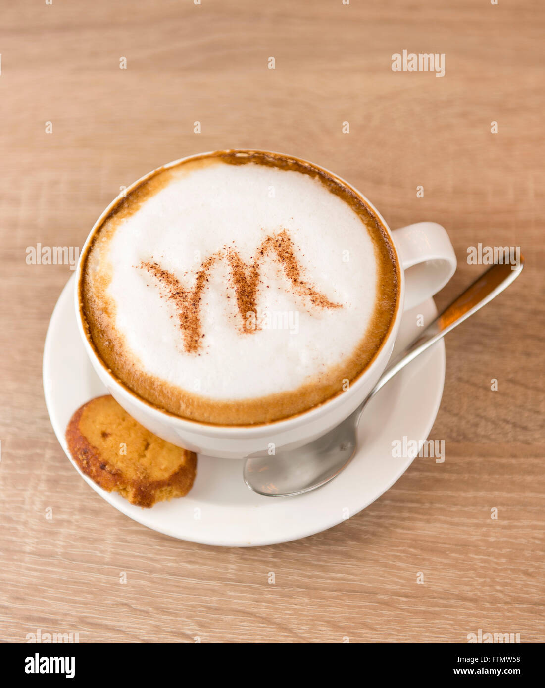 A coffee cappuccino latte with a letter M written into the milk foam. - Stock Image