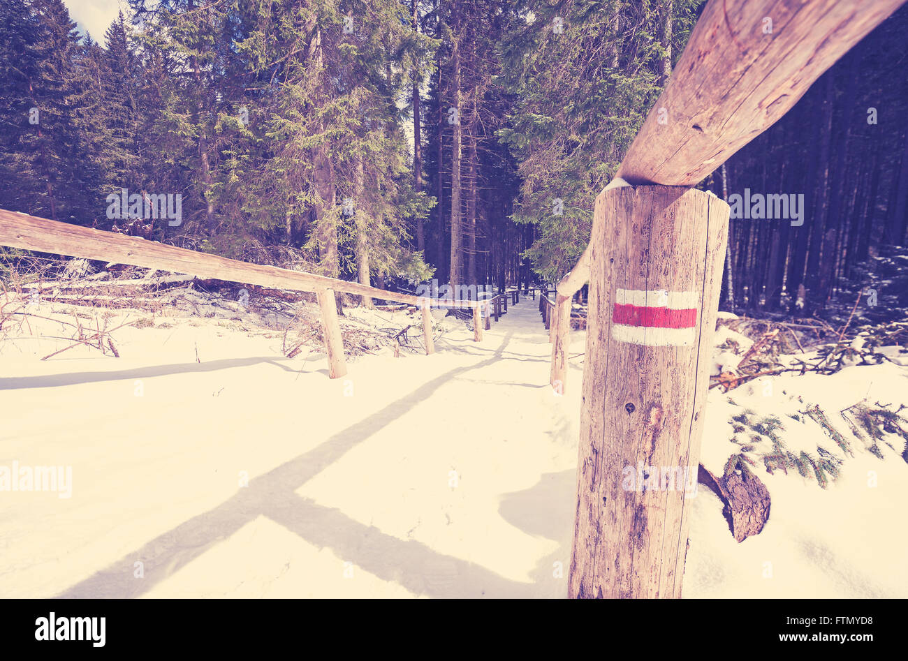 Vintage toned trail sign painted on perch, winter in Tatra mountains, Poland. Stock Photo
