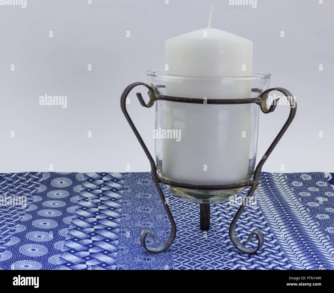 Close up of one white unlit candle against white and blue linen print background - Stock Image