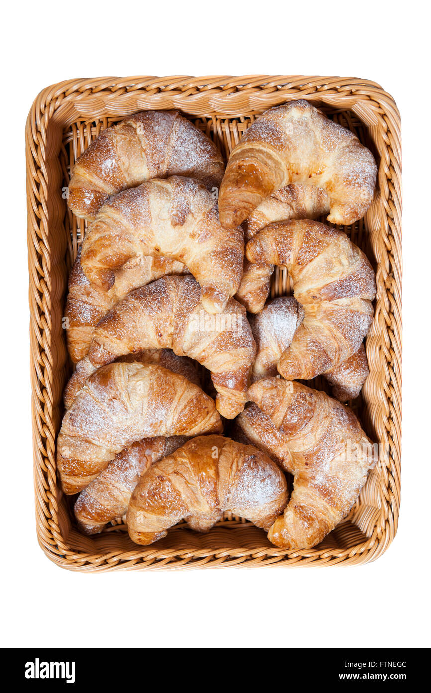 Croissants dusted with white icing sugar on display in a woven basket with a white background - Stock Image