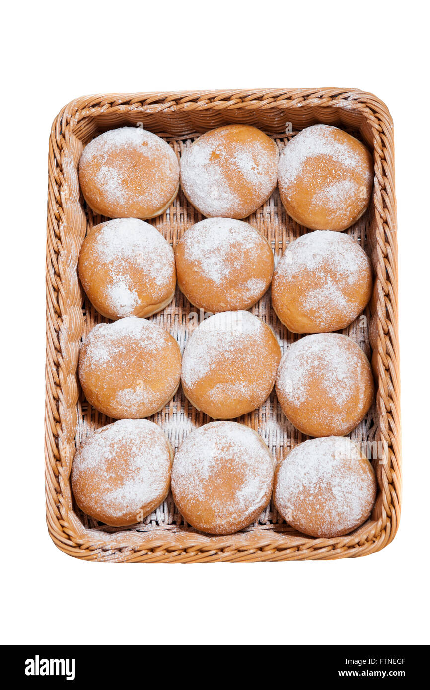 Jelly Doughnuts dusted with sugar on display in a woven basket on a white background - Stock Image