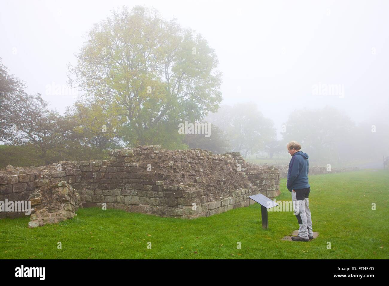 Hadrian's Wall. Tourist looking at Turret 52A in fog. Banks, Cumbria, England, United Kingdom, Europe. - Stock Image