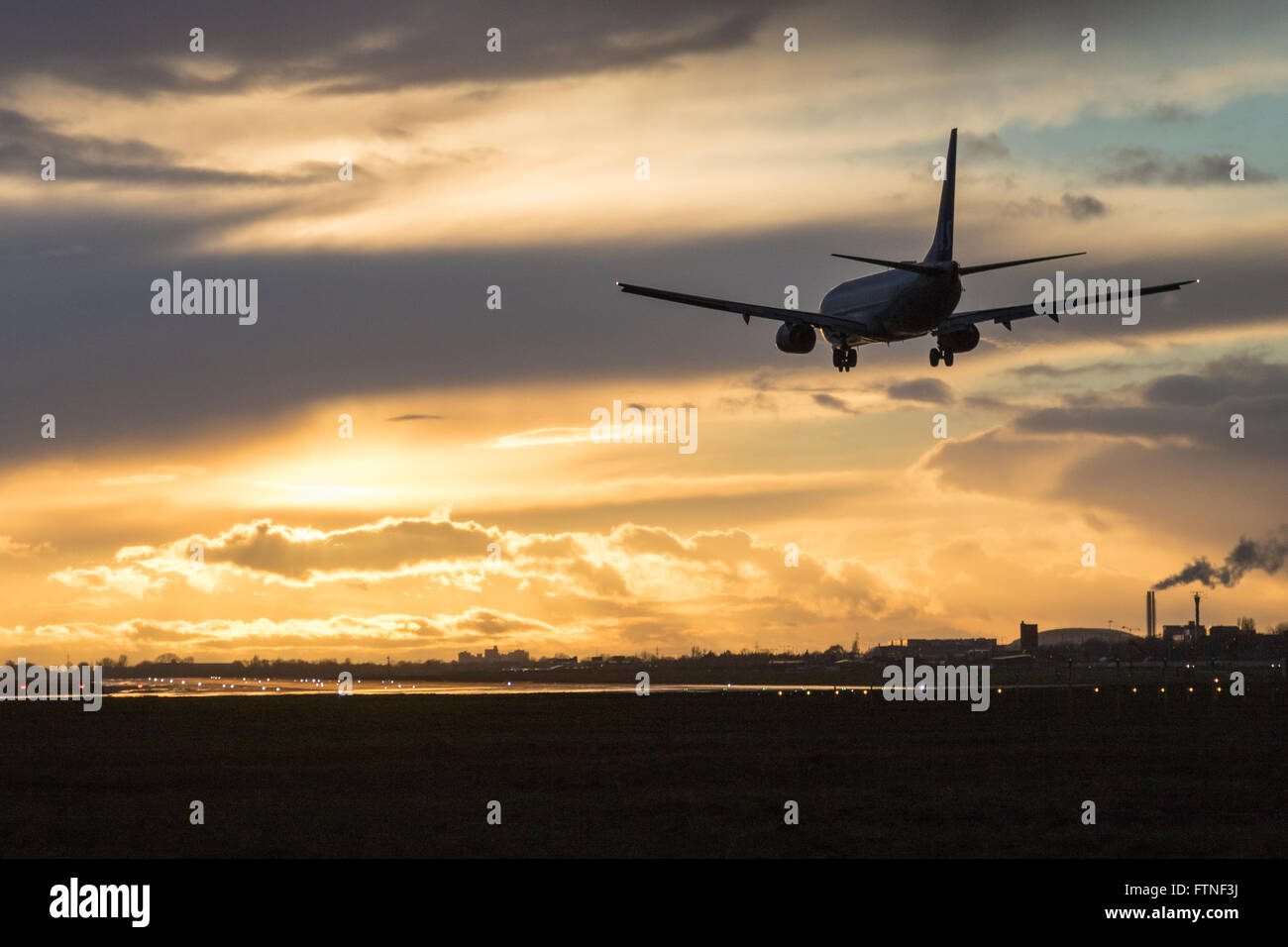 A Boeing 737 is silhouetted against clouds illuminated by the setting sun, about to land at London Heathrow. - Stock Image