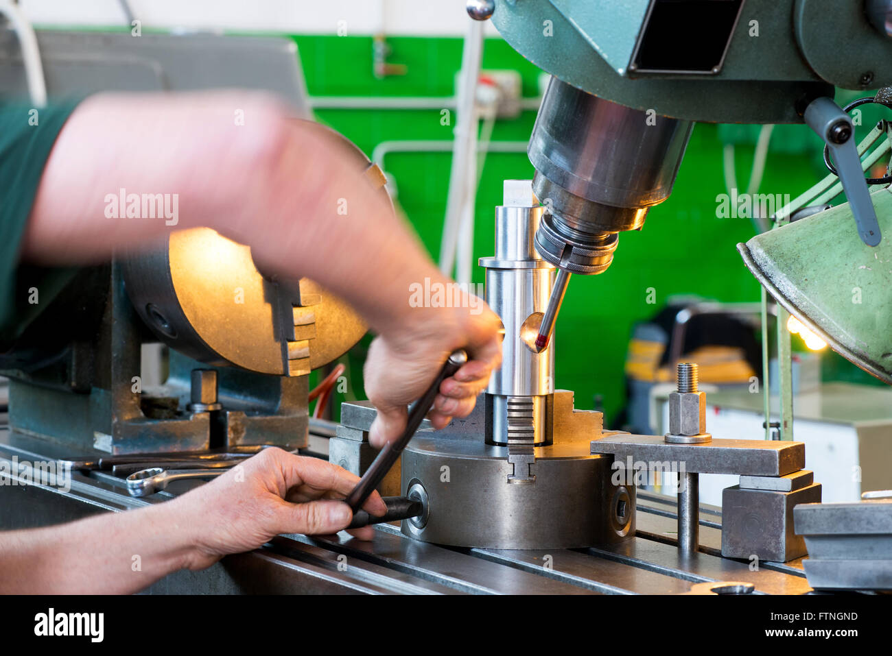 Close up view of the arms of a blue collar worker working on industrial machinery in an engineering factory or workshop - Stock Image