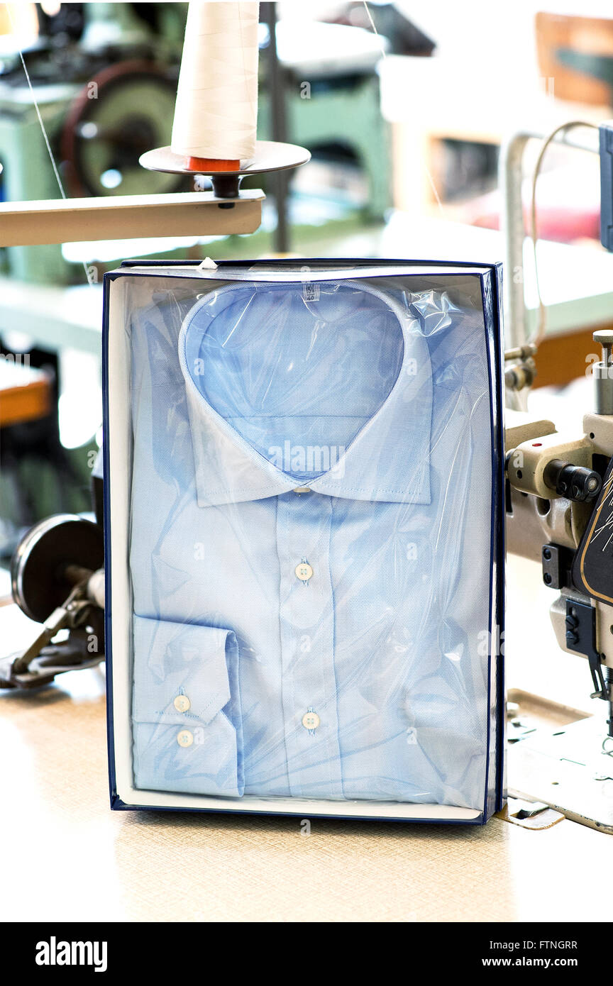 Handmade button down shirt in retail packaging displayed upright in a box in a tailors shop - Stock Image