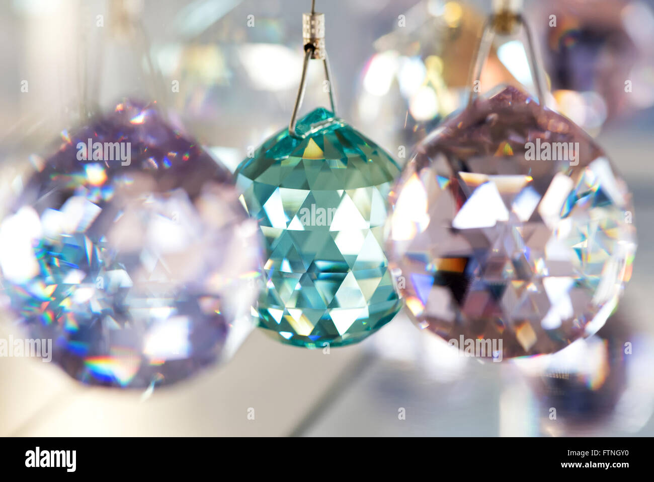 Faceted crystal ball decorations in lilac and blue hanging in a store, close up detailed view with focus to the - Stock Image