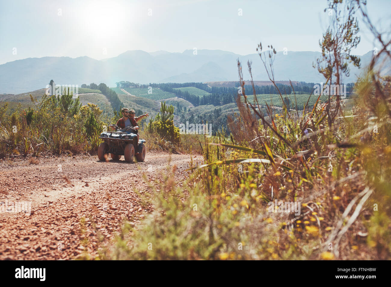 Young couple having fun on quad bike ride on a summer day. Young man driving the ATV girlfriend pointing at something - Stock Image