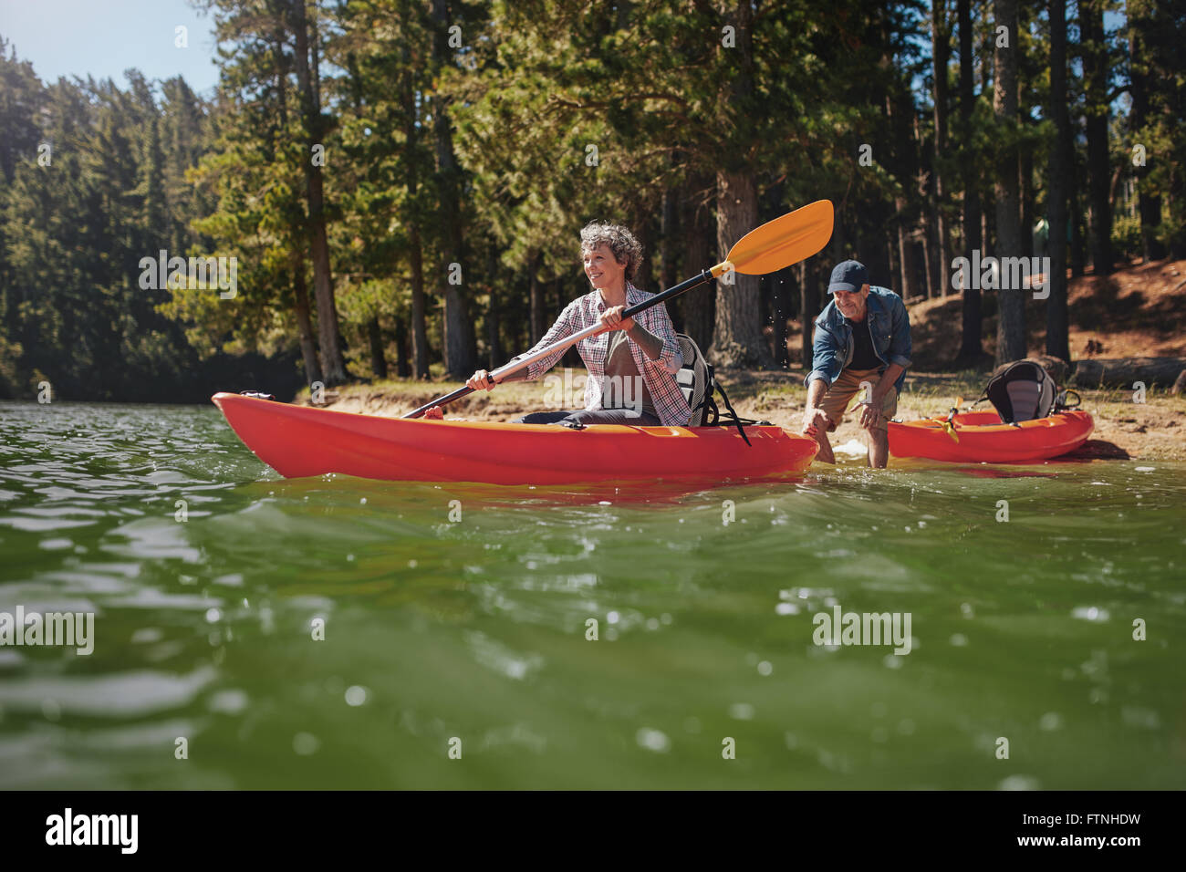 Portrait of mature woman canoeing in the lake with man about to catch the kayak from behind. Senior couple having - Stock Image