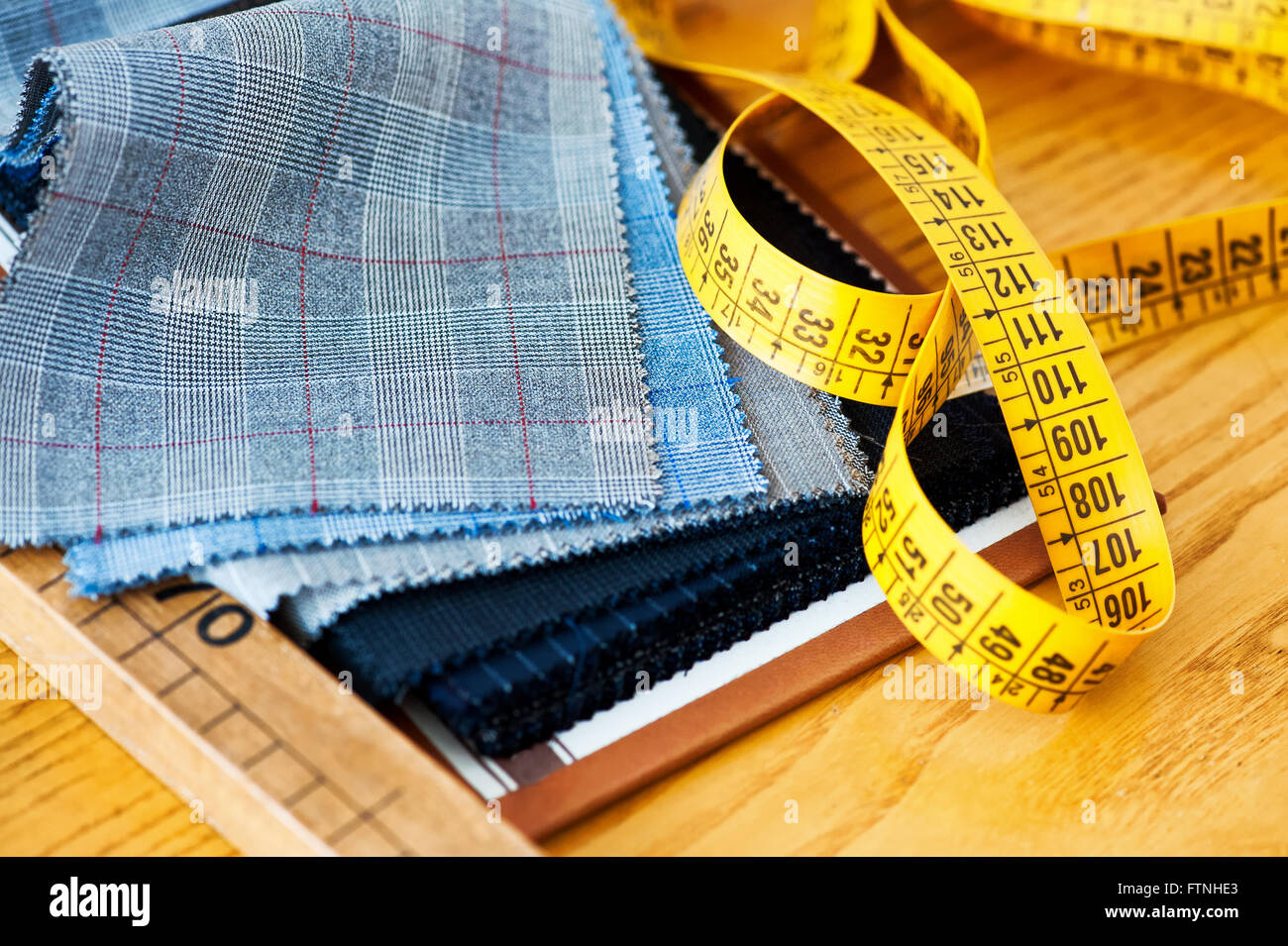 Sample fabric swatches on a tailors workbench with a yellow tape measure showing the tools of the trade in a close - Stock Image