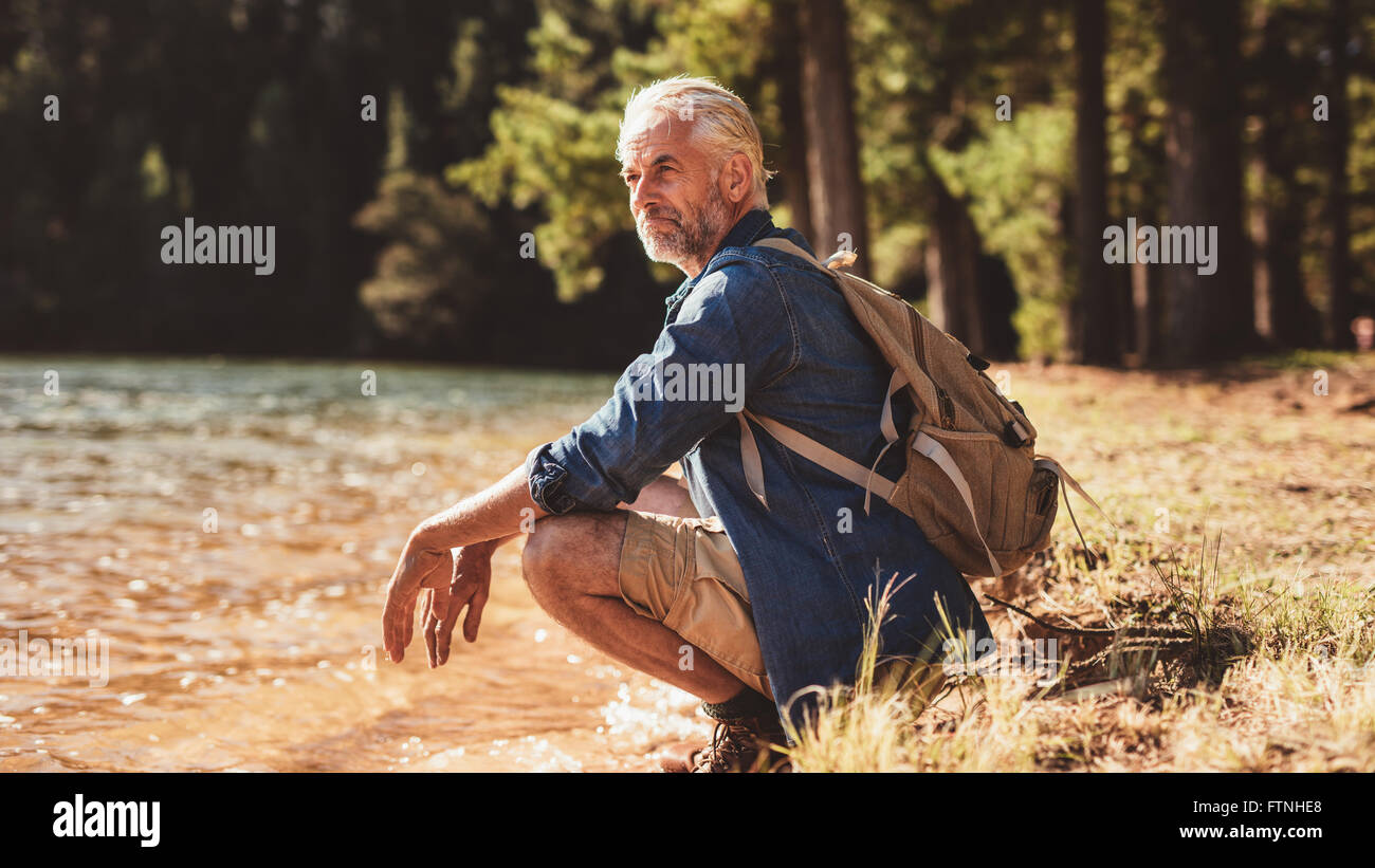 Portrait of a senior man with backpack sitting next to a lake admiring the view. Mature man taking a break from - Stock Image