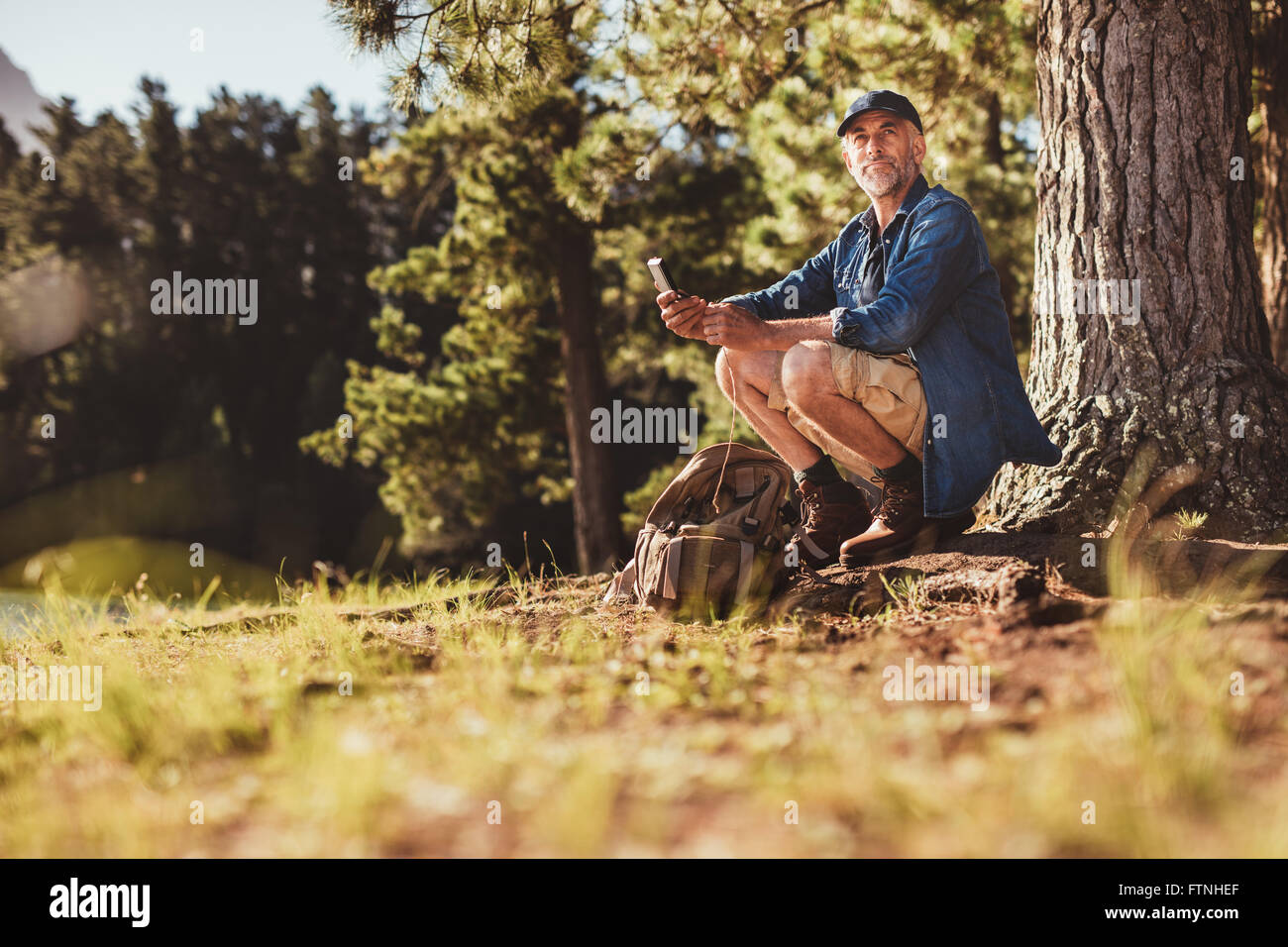 Portrait of senior caucasian man sitting outdoors in forest with a compass. Mature man hiking in nature looking - Stock Image