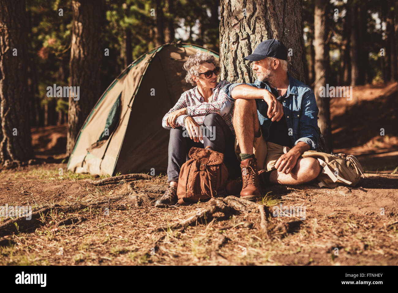 Portrait of happy senior couple sitting together under a tree on summer day. Mature man and woman near the tent, - Stock Image