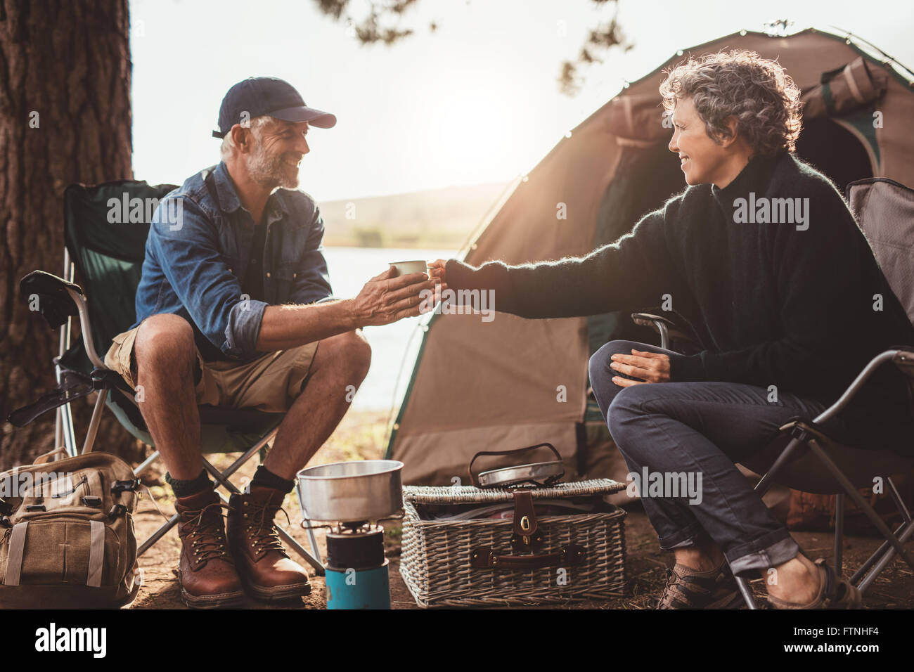 Portrait of senior woman giving a cup of coffee to man at campsite. Both sitting outside tent. Mature couple camping - Stock Image