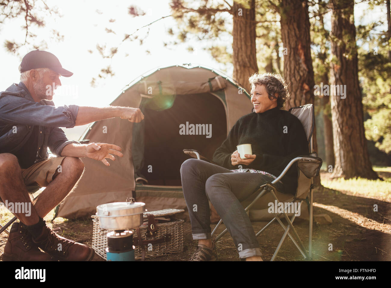 Portrait of senior campers having a good time during a camping trip on a summer day. Smiling mature couple sitting - Stock Image
