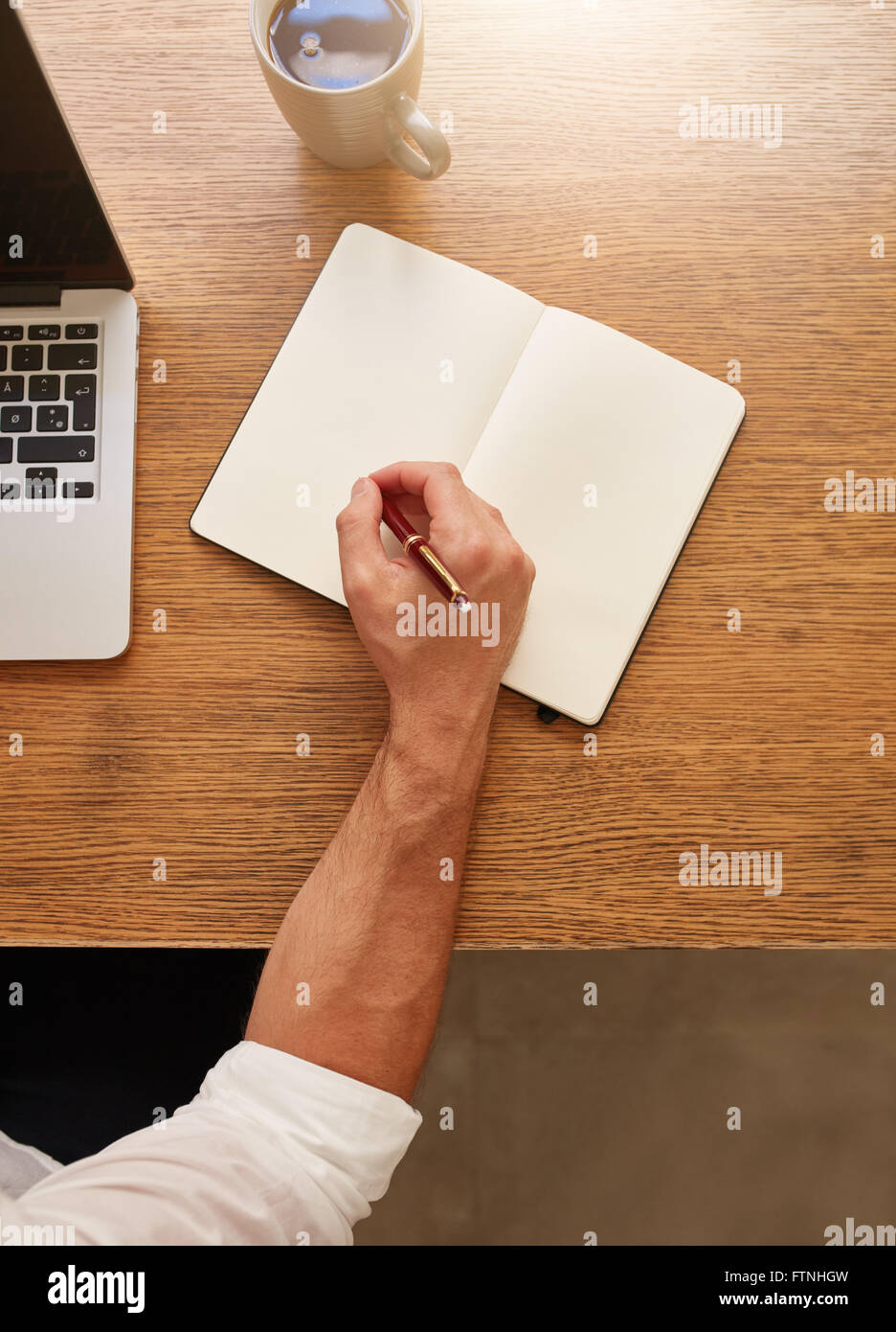 Top view shot of man making some notes in his diary while sitting at his working place. - Stock Image