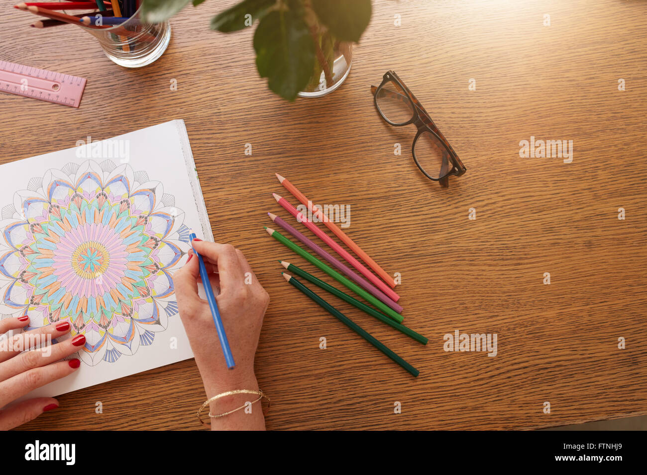 Close up image of female hands drawing in adult colouring book on a table at home. - Stock Image