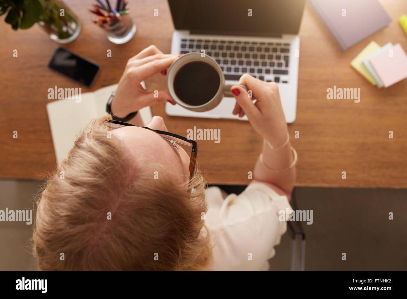 Overhead view of woman drinking coffee while sitting at her work desk at home office. - Stock Image