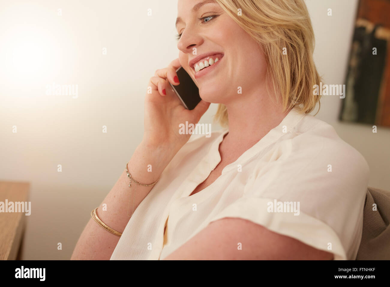 Close up of a happy woman talking on mobile phone. Caucasian female in conversation on cellphone. - Stock Image