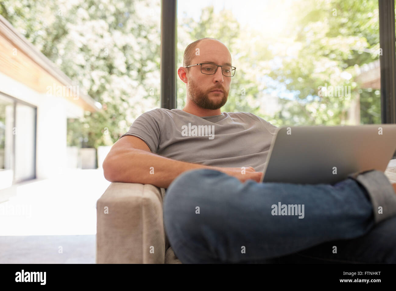 Portrait of mature caucasian man sitting on a sofa and working on laptop. Man surfing internet on laptop computer. - Stock Image