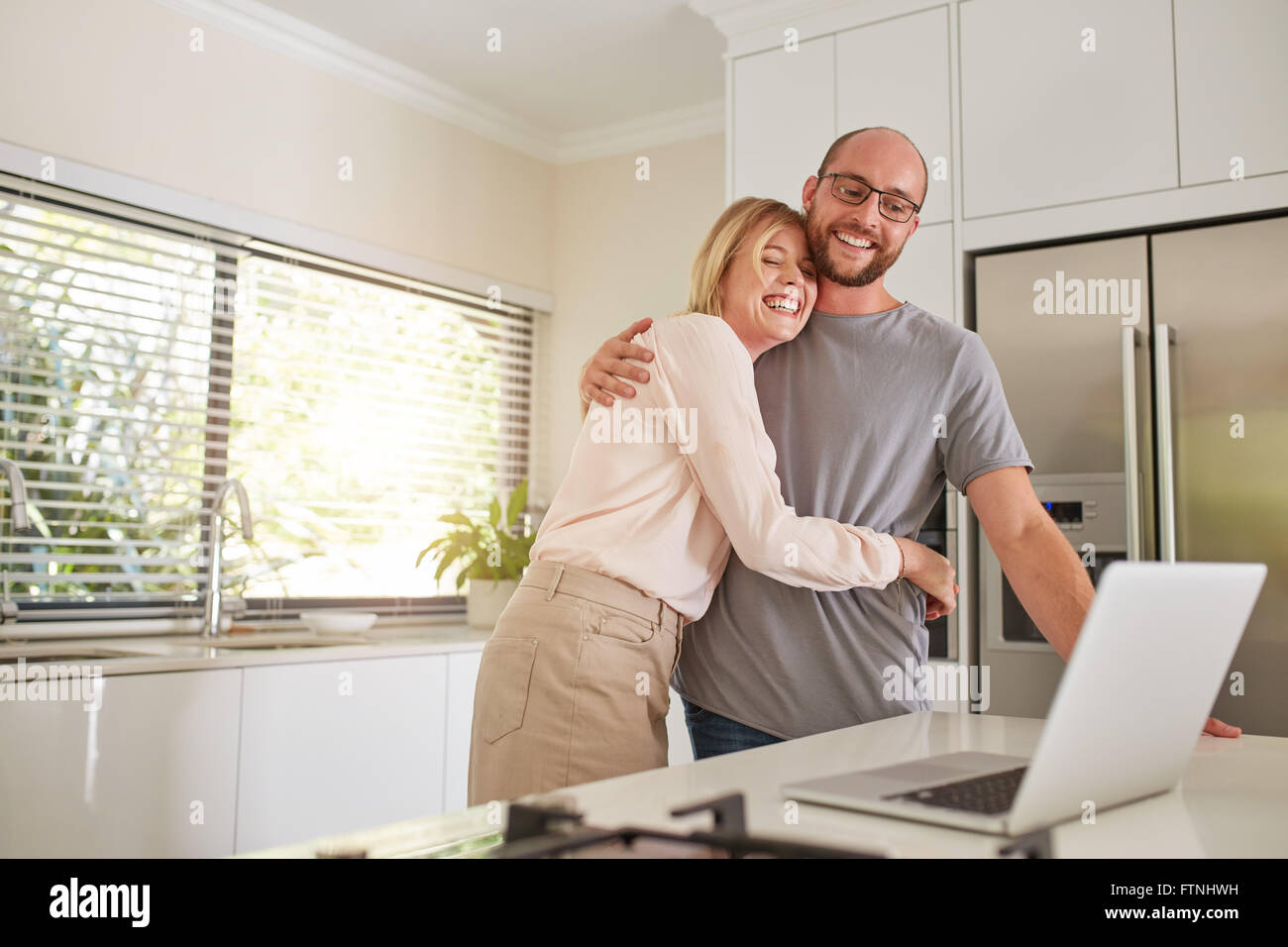 Indoor shot of loving couple in kitchen with a laptop. Mature man and woman embracing each other and smiling with - Stock Image