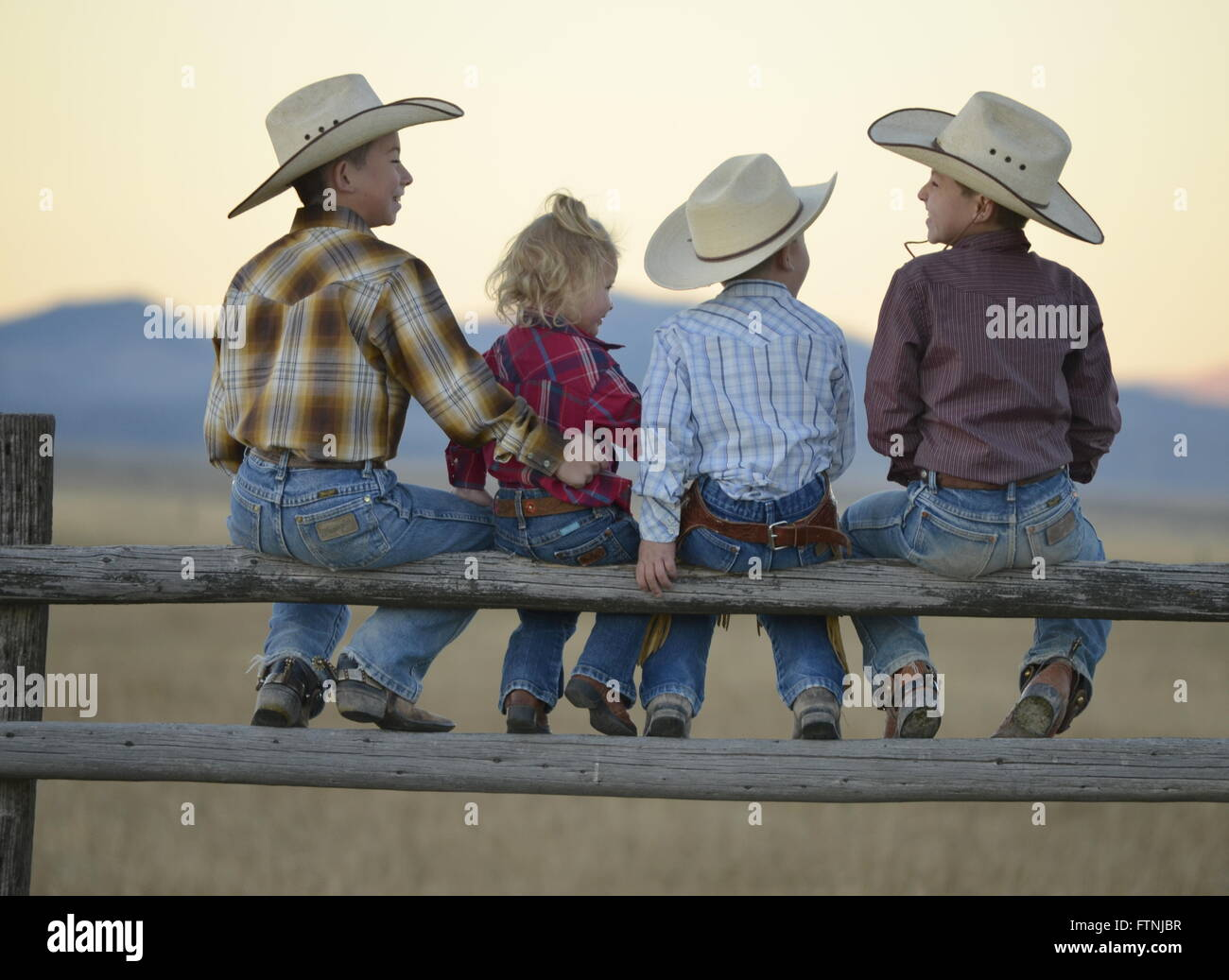 Cowboy kids sitting on old wooden fence with cowboy hats on. - Stock Image