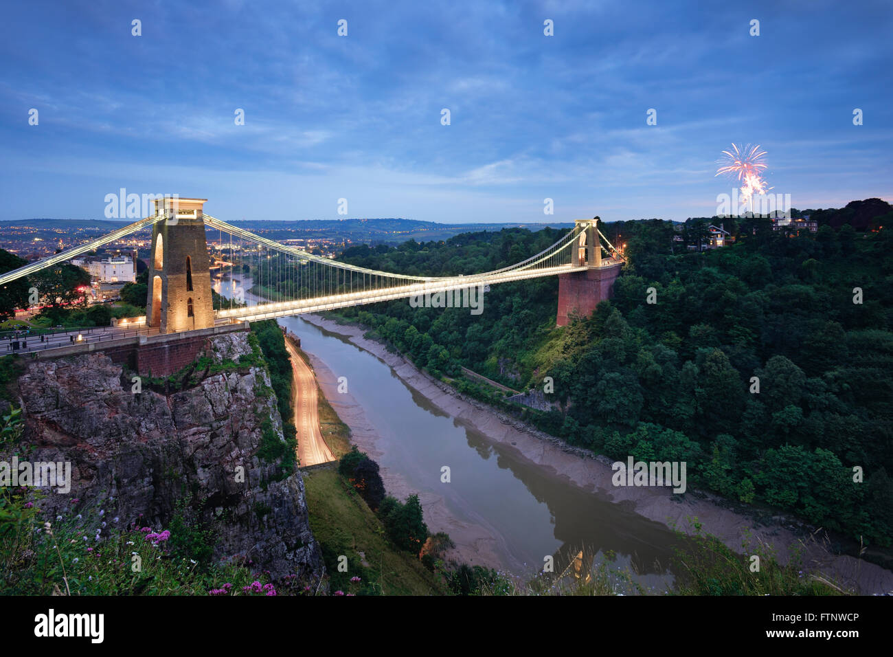 A firework is set off from Ashton Court with the Clifton Suspension bridge in the foreground. Stock Photo