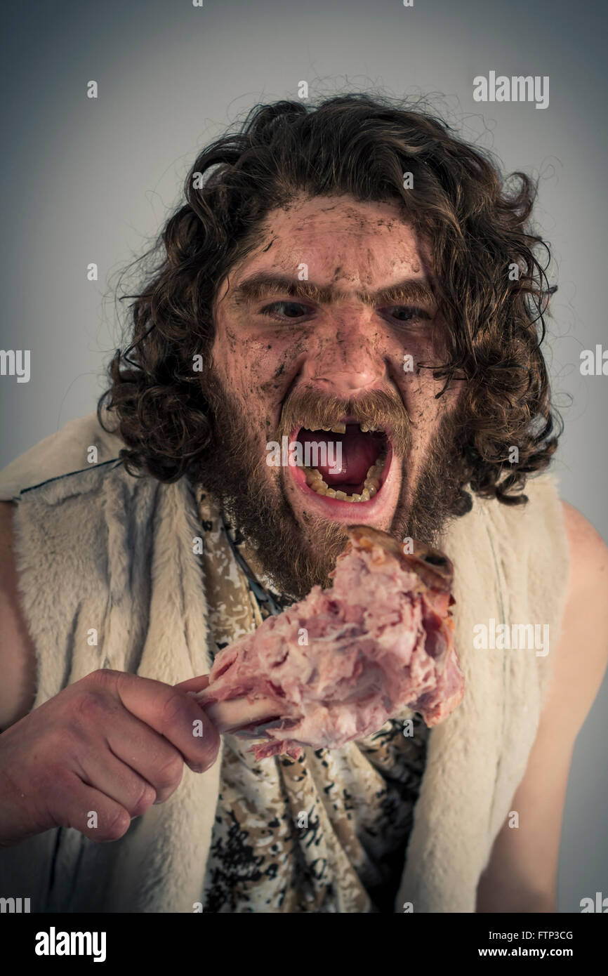 Silly hungry cave man eating ham on the bone - Stock Image