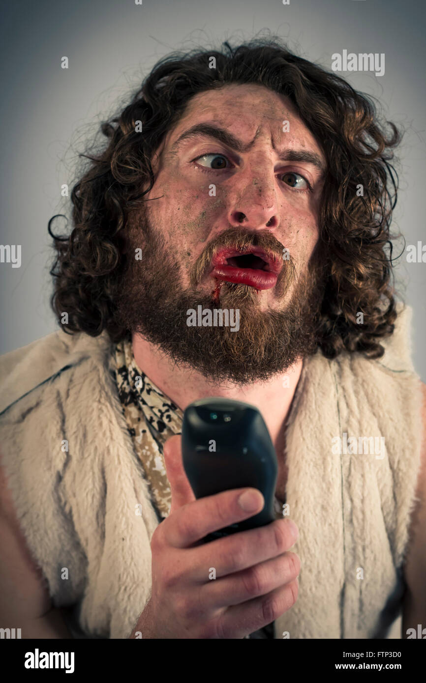Silly grunting cave man confused by television remote - Stock Image
