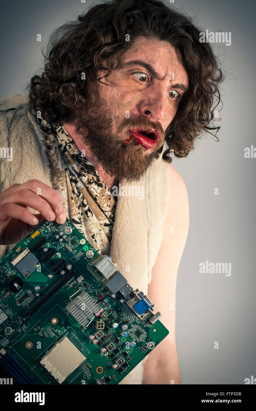 Silly grunting caveman confused by modern computer technology - Stock Image