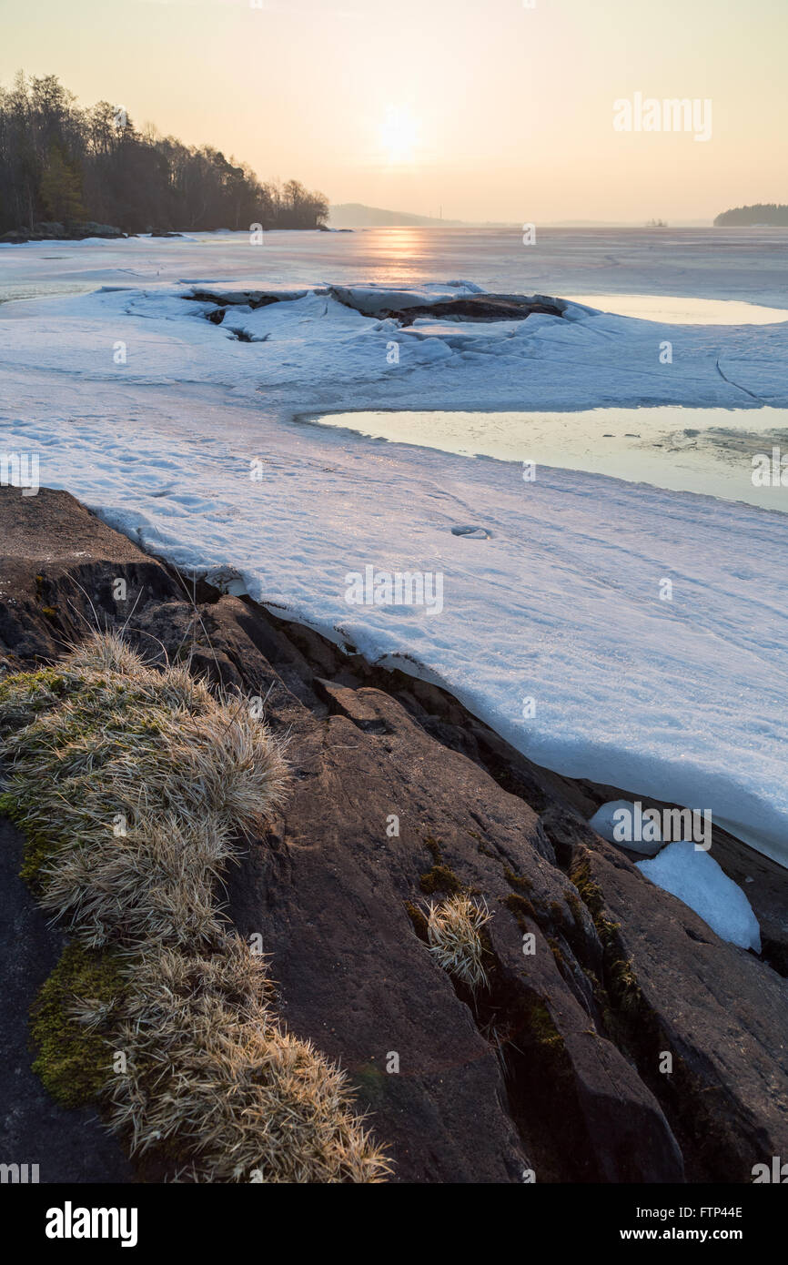 Landscape of rock, frozen lake and cracked ice in Finland in the spring at dawn. - Stock Image