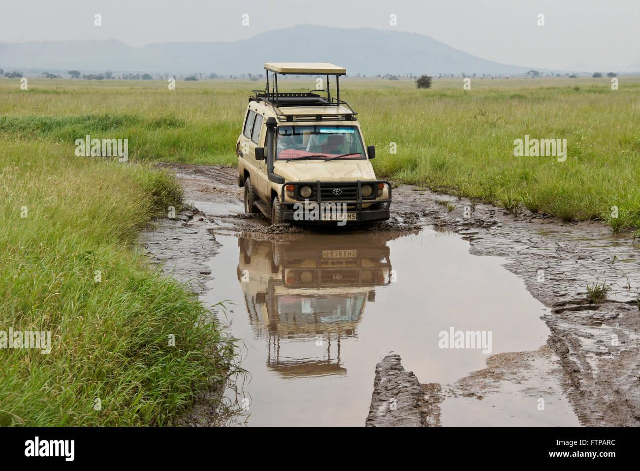 Safari vehicle driving through a mud hole on the Serengeti, Tanzania - Stock Image