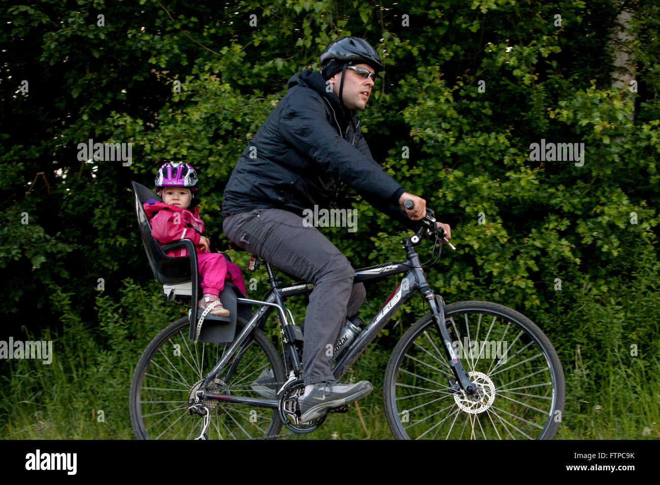 father on bicycle with his daughter in a child bike seat on a trip - Stock Image