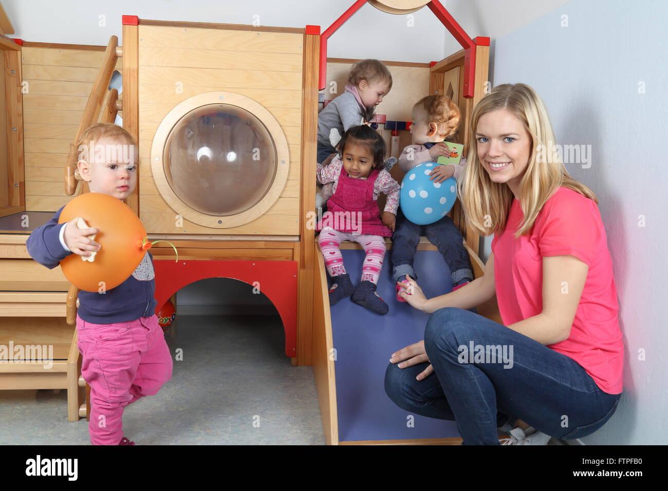 A Nursery nurse with 4 Kids on a indoor slide - Stock Image