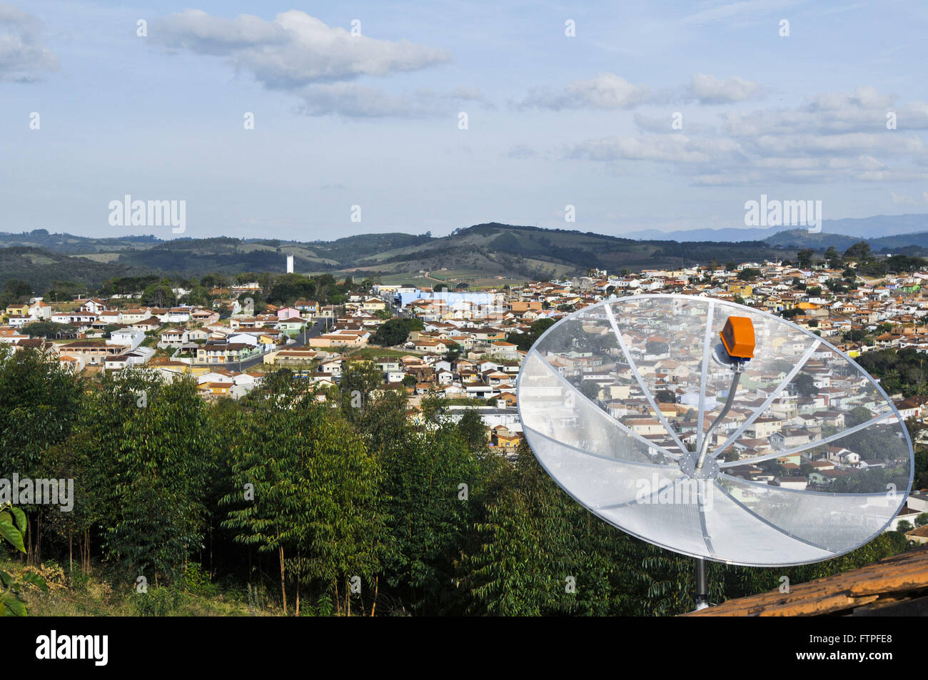 Highlight of parabolic antenna housing and city view in the background - Stock Image