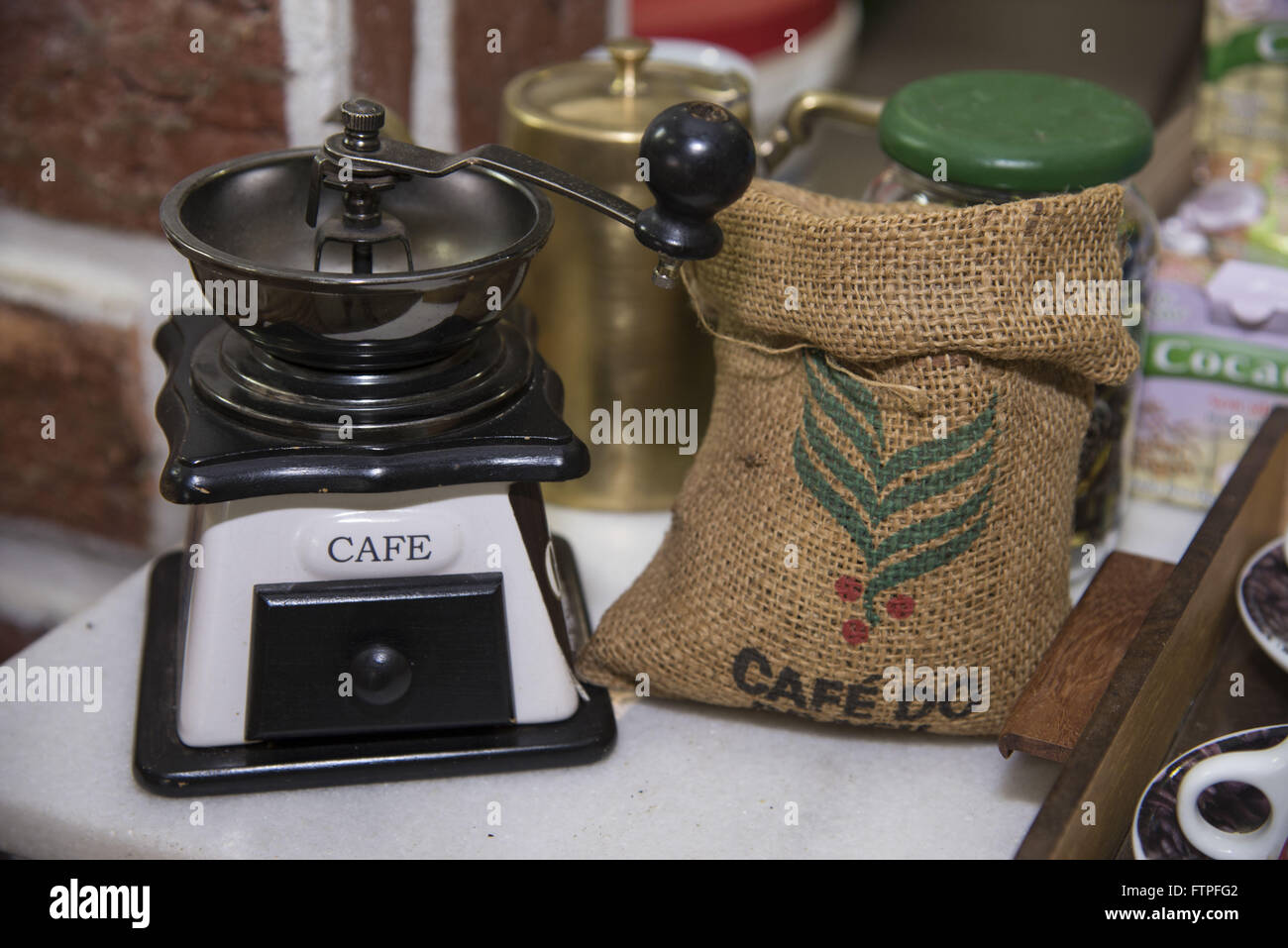 Grinder and sack with coffee beans roasted in store commercialization Cafe Carmo de Minas - Stock Image