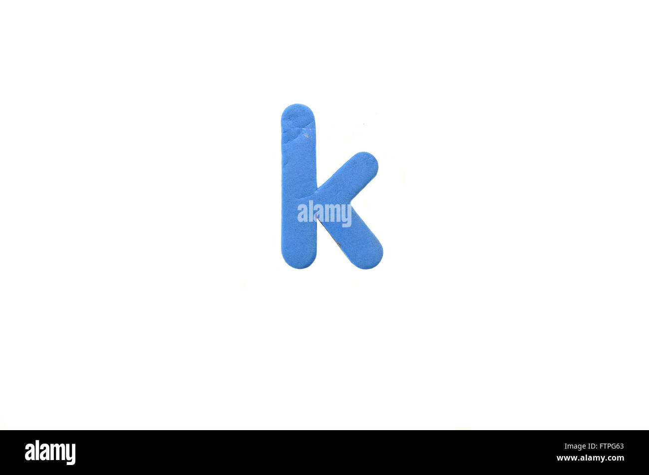 A letter K fridge magnet photographed against a white background. - Stock Image