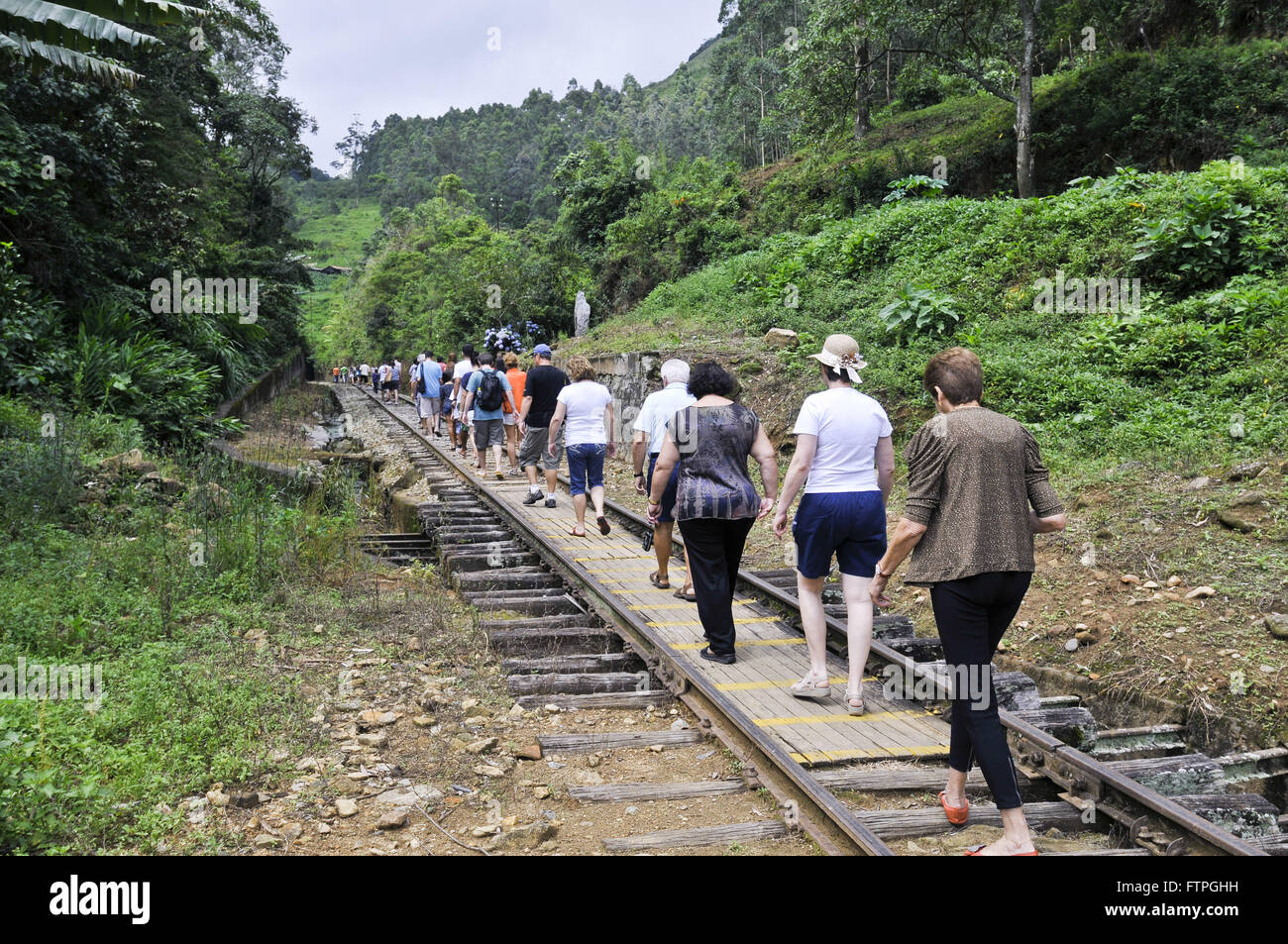 Tourists walking on the tracks in the direction of the tunnel Mantiqueira - Stock Image