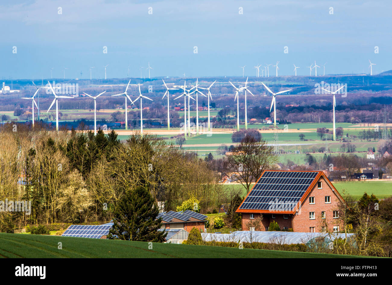 Private house with solar energy plant on the roof, wind park