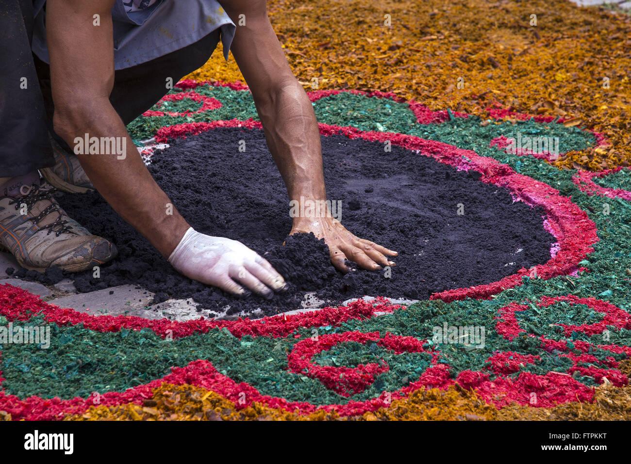 Fiel decorando rua com tapetes de serragem colorida para procissao da Semana Santa - Stock Image