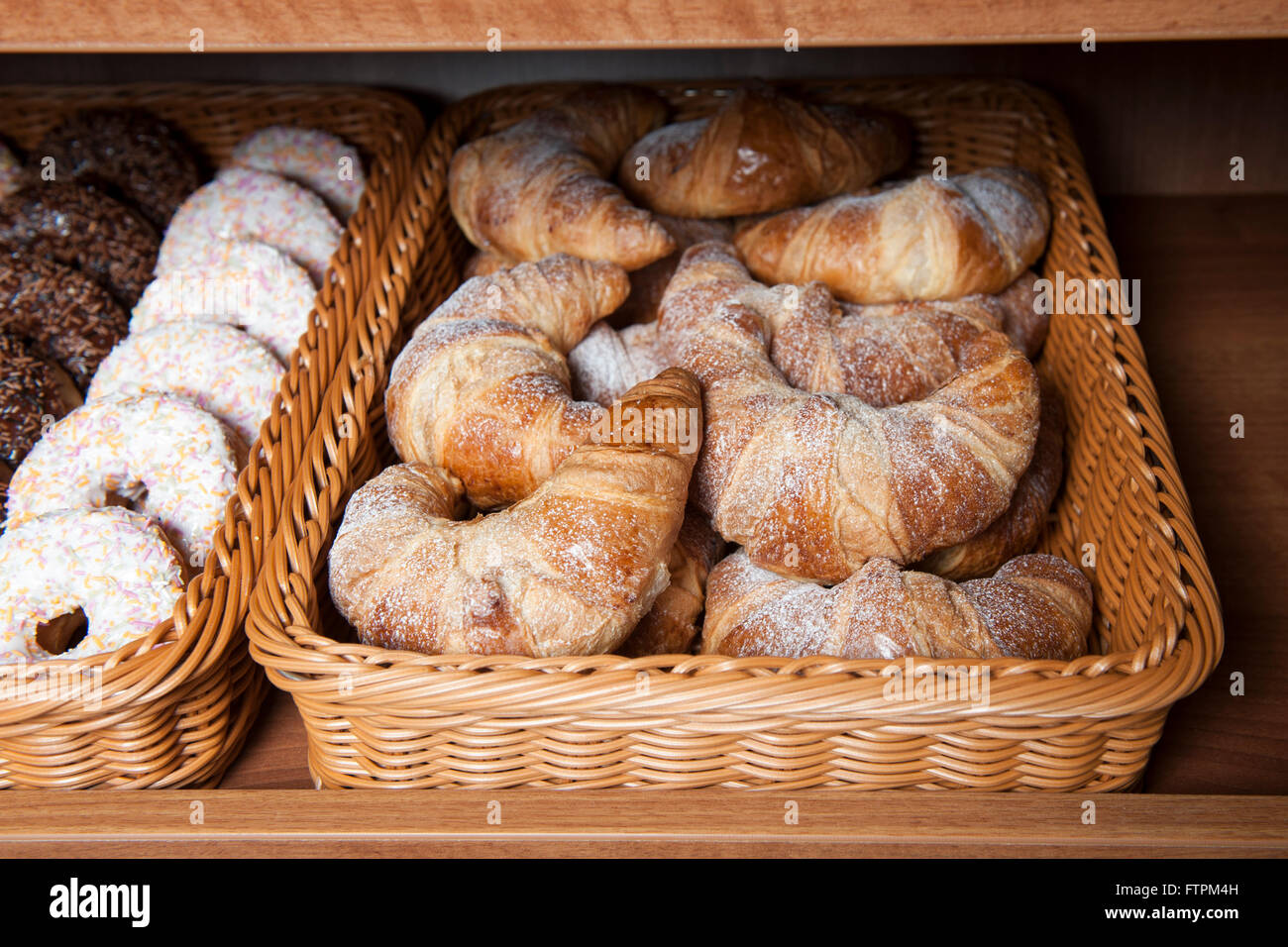Croissants dusted with white icing sugar on display in a woven basket next to a basket of iced doughnuts with sprinkles - Stock Image