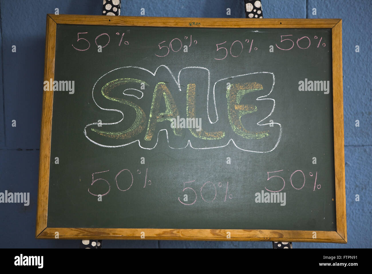 Blackboard with liquidation announcement chalked in English - Stock Image