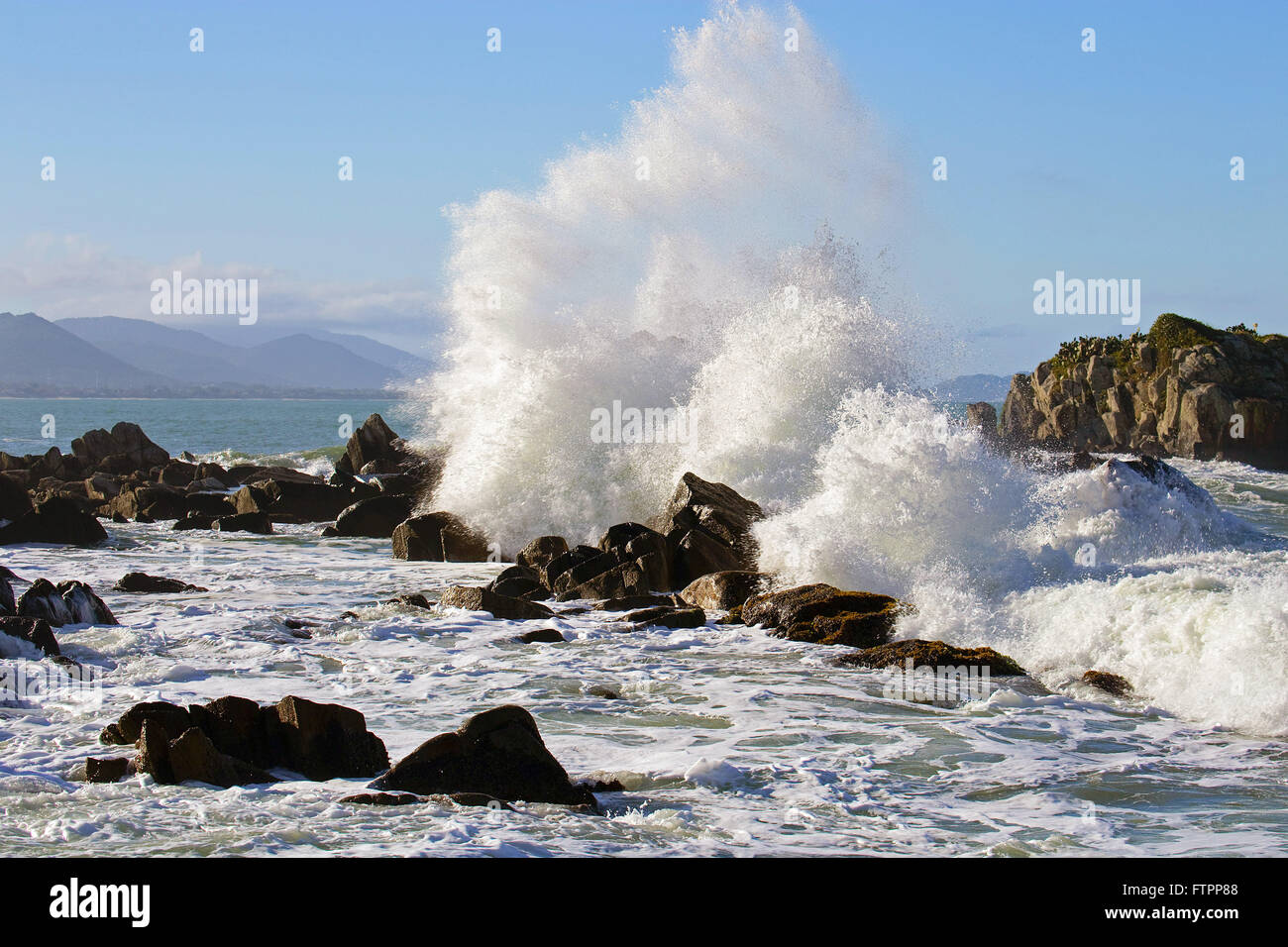 Ocean waves crashing on the rocks of the beach Armacao - south of the island - Stock Image