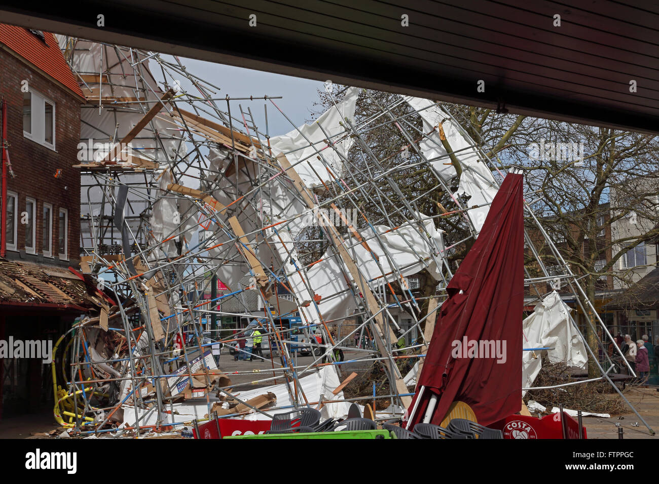Collapsed scaffolding all bent and twisted laying at an angle where the wind has blown it away from the building - Stock Image