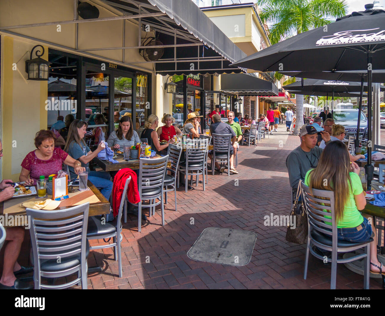 Outdoor dining at sidewalk cafe on First Street at Fords Garage Restaurant in downtown Fort Myers on the Gulf Coast - Stock Image