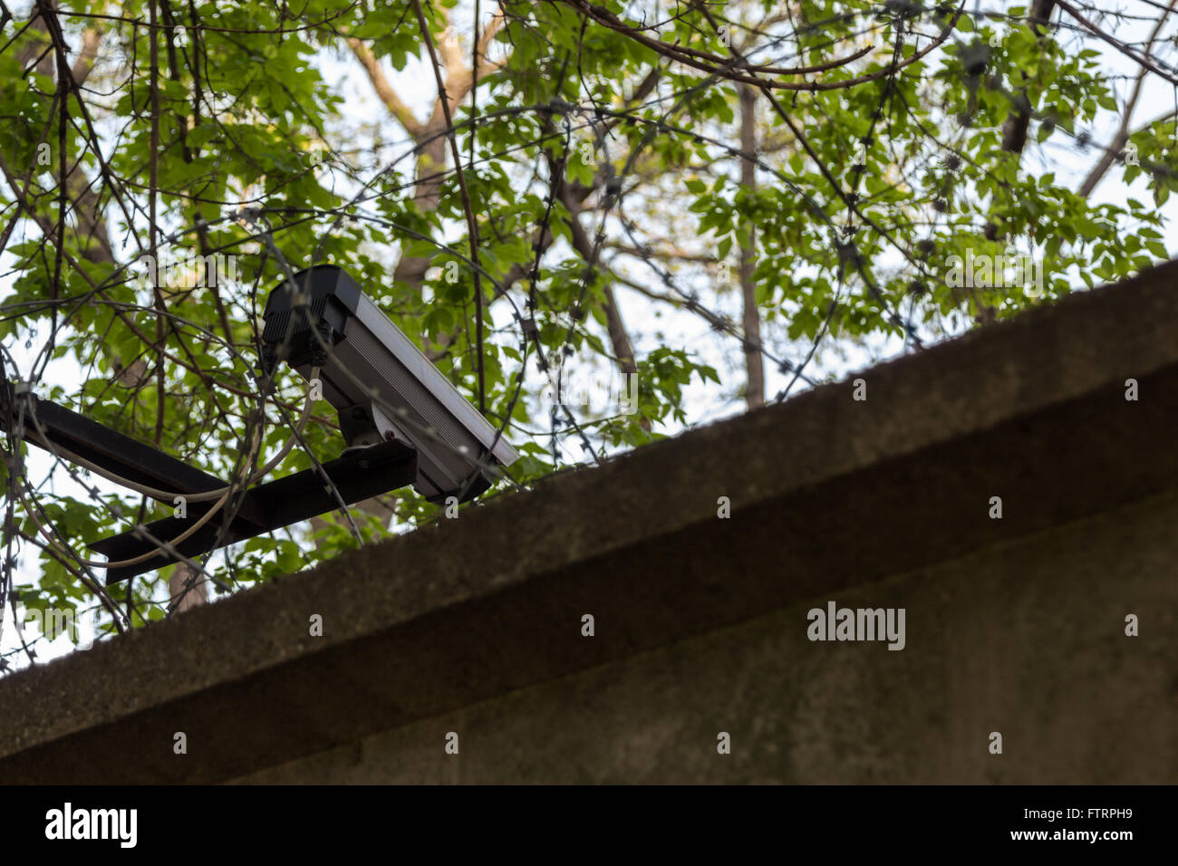 surveillance camera on a concrete fence with barbed wire Stock Photo