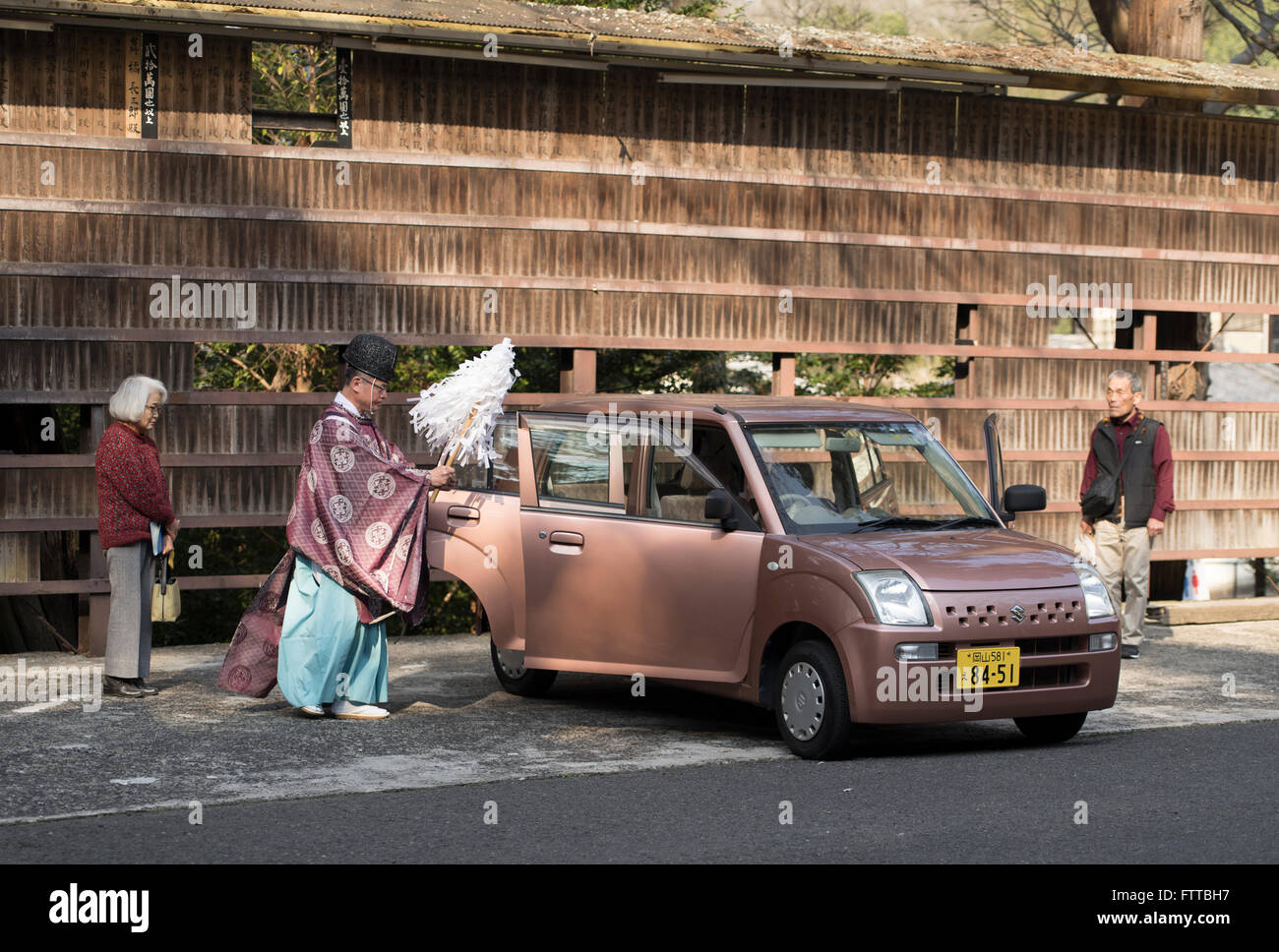 Shinto priest blesses a new car as the owners watch at Kibitsu Shrine, Okayama Prefecture, Japan. - Stock Image