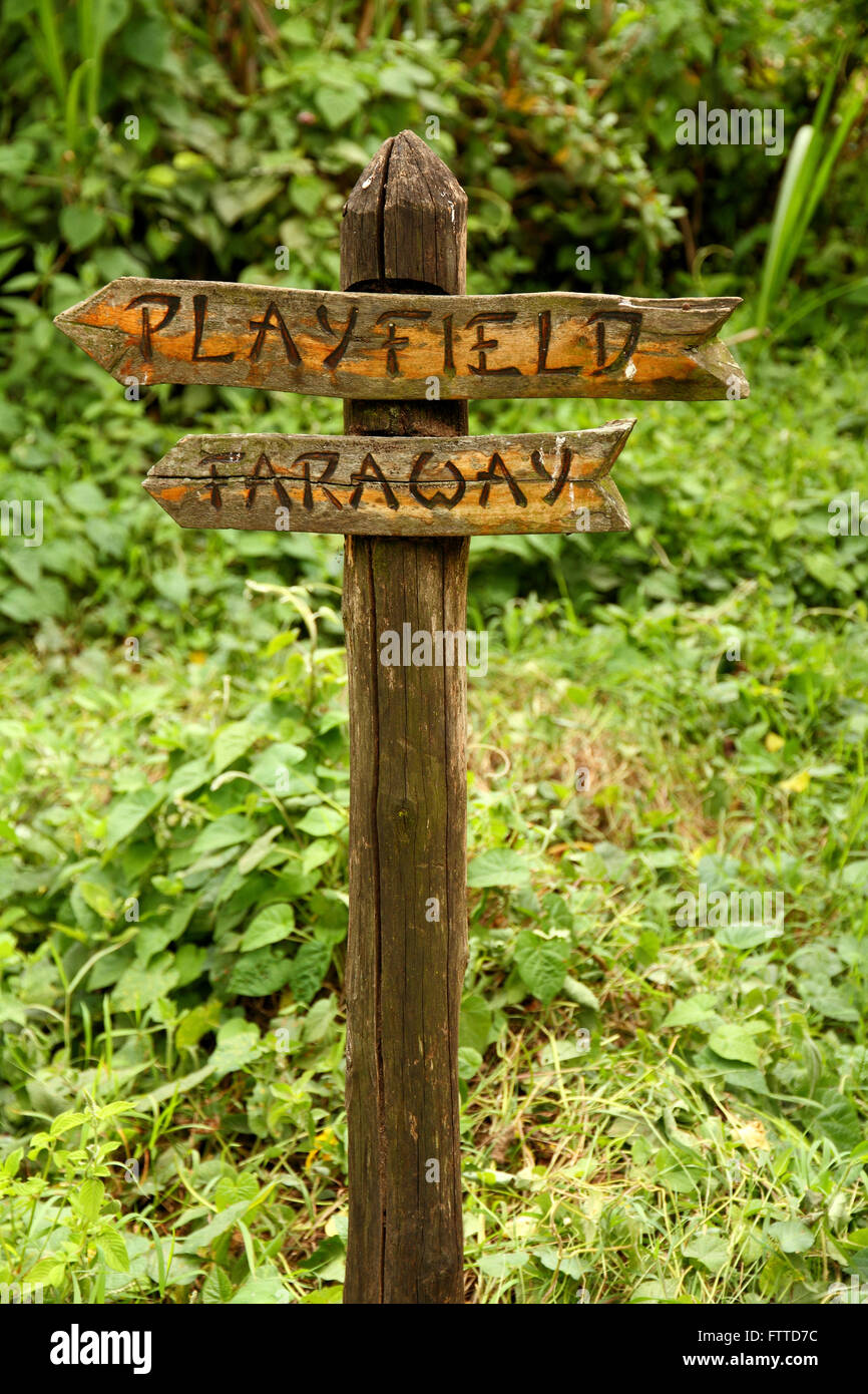 A unique and funny wooden sign pointing to two places; 'faraway' and 'playfield' - Stock Image