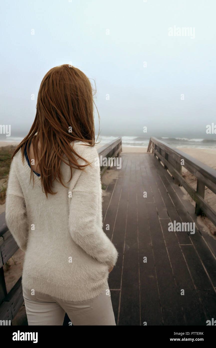 Woman walking on wooden boardwalk at beach - Stock Image
