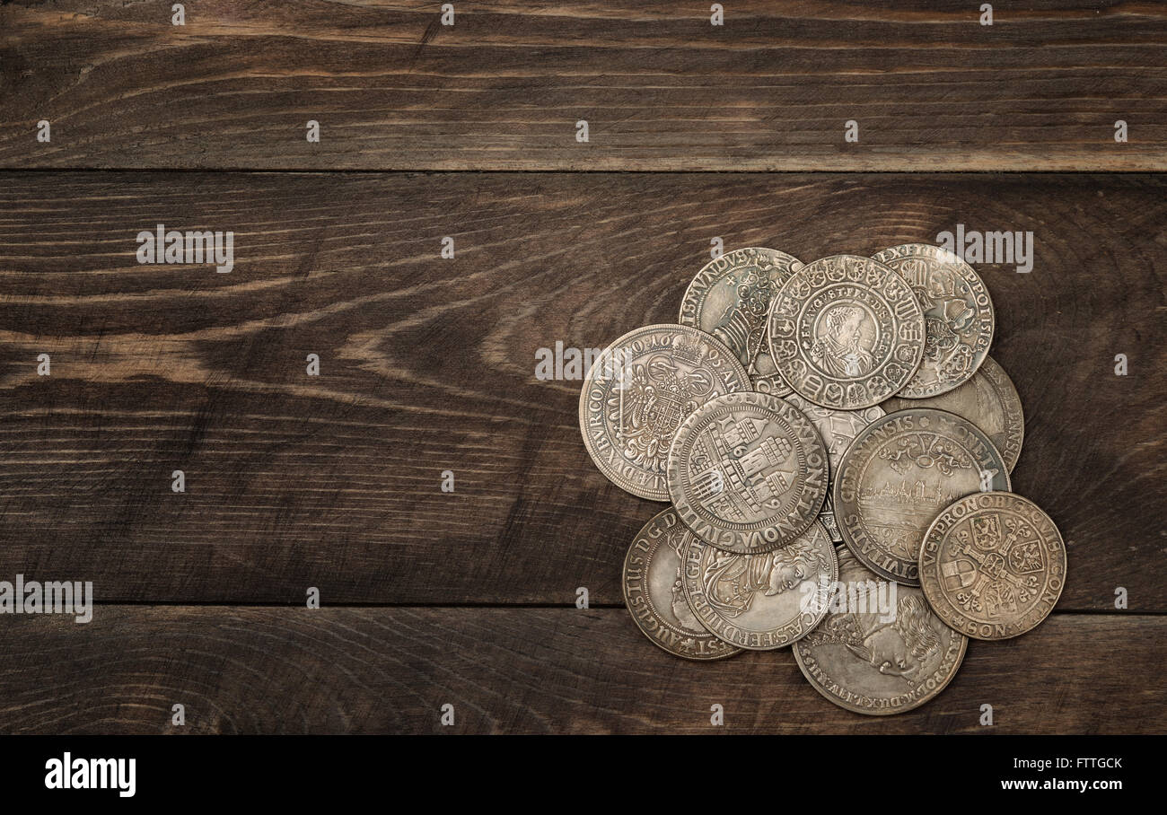 Ancient silver coins on dark wooden background - Stock Image