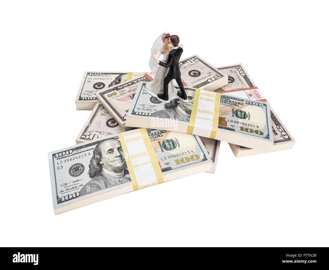 Photograph of bride and groom figurines dancing on top of stacks of U.S. paper currency. - Stock Image